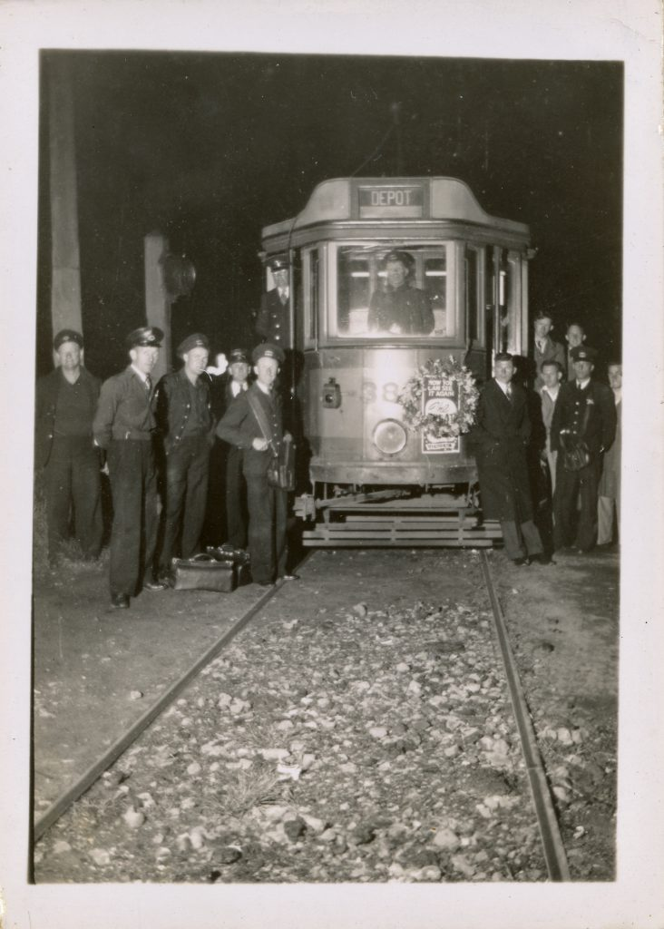 Photo of group of staff members posing in front of the #316 during its' final service.