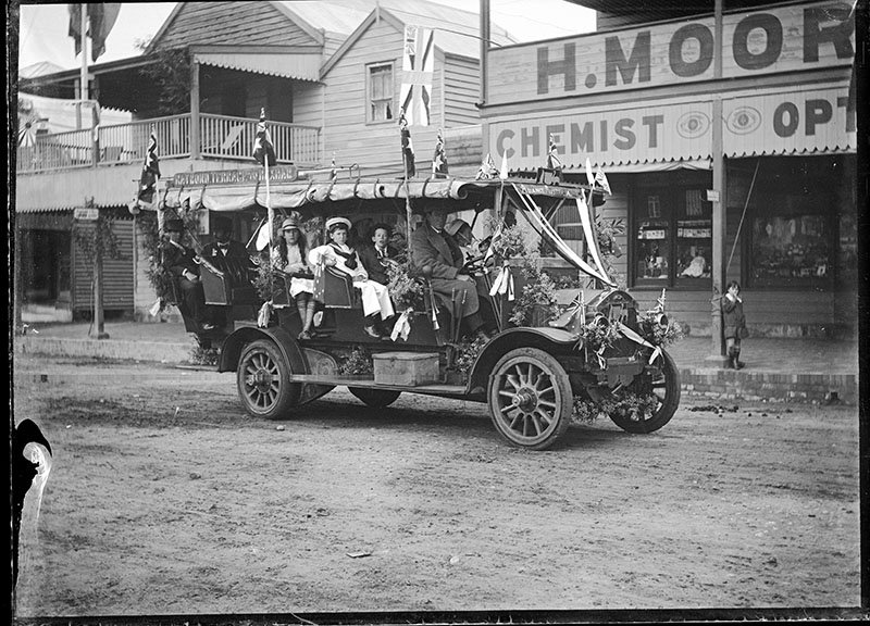 Photo shows a decorated charabanc in King Street, Raymond Terrace as part of the parade. Sign on vehicle suggests it was used for public transport between Raymond Terrace and Hexham.