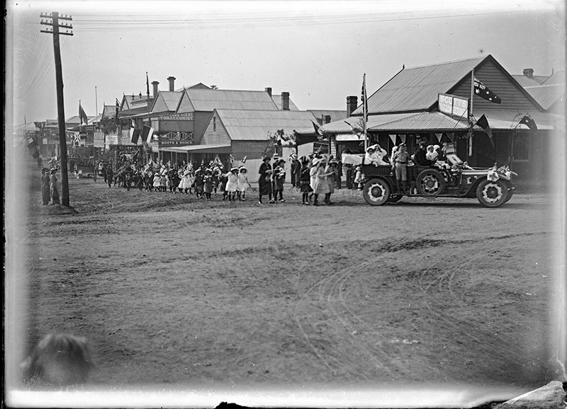 Photo shows parade procession on King Street in Raymond Terrace with children and cars. The shot is taken from the western end of the street.