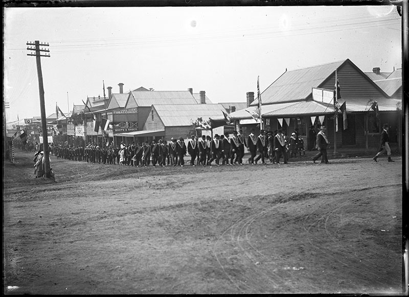 Photo shows members of the Freemasons marching down King Street in Raymond Terrace.